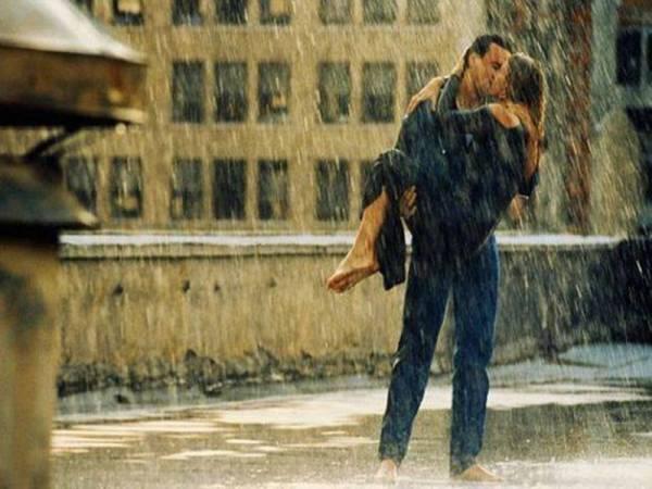 Парень и девушка целуются под дождем